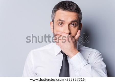I am shocked! Surprised mature man in shirt and tie covering mouth with hand and looking at camera while standing against grey background - stock photo
