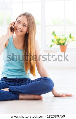I am so glad to hear you! Cheerful teenage girl talking on the mobile phone and smiling while sitting on the floor at her apartment - stock photo