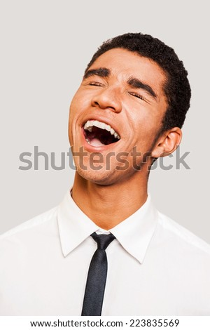 I am so lucky! Happy young Afro-American man in shirt and tie with open mouth and closed eyes standing against grey background - stock photo