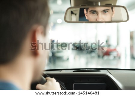 I am sure with my car choise. Hansome young men sitting at front seat of the car looking at review mirror - stock photo