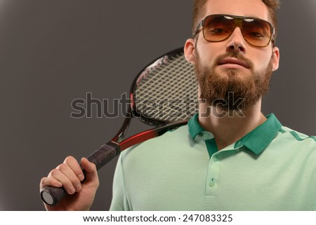 I am the best. Cropped image of young sportsman holding tennis racket and looking at camera while standing against grey background with copy space - stock photo