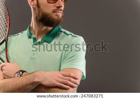 I am the best. Cropped image of young sportsman holding tennis racket and looking away while standing against grey background with copy space - stock photo