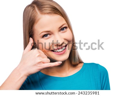 I am waiting for your call! Cheerful young women gesturing phone sign and smiling while standing against white background - stock photo
