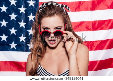 I am watching you. Beautiful young woman looking over sunglasses while standing against American flag - stock photo