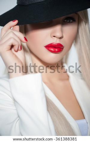 I am your dream. Waist up portrait of attractive blond young woman wearing black hat. She is touching it and looking camera with passion - stock photo