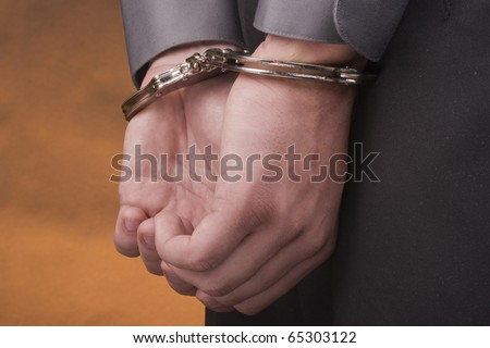 I arrested his hands handcuffed behind his back. - stock photo
