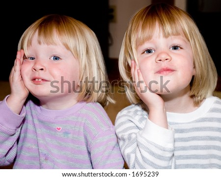I asked these two twins girls to touch their cheeks together.  I meant for them to lean against each others cheeks but this is what I got! - stock photo