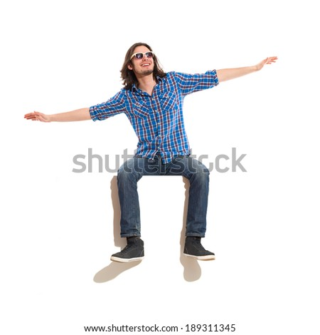 I believe i can fly. Young man sitting on a banner with arms outstretched and looking away. Full length studio shot isolated on white. - stock photo