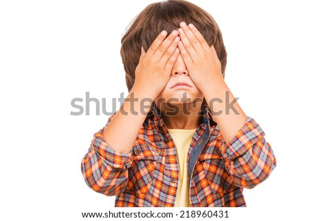 I can see nothing! Cute little boy covering eyes with hands while standing isolated on white - stock photo