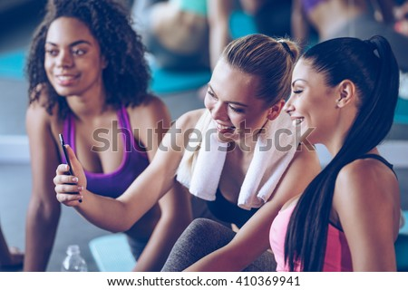 I can see progress in my workouts! Beautiful young women in sportswear discussing something with smile and using smartphone while sitting on exercise mat at gym