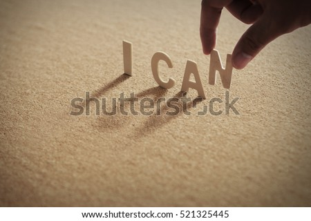 I CAN wood word on compressed board,cork board with human's finger at N letter