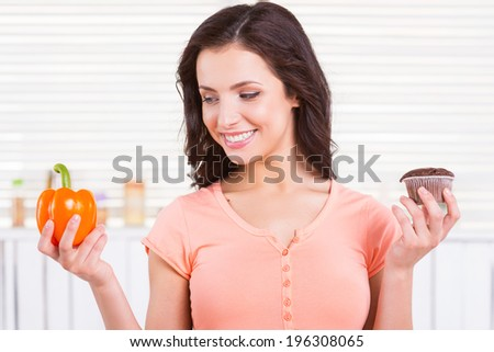 I choose healthy food. Cheerful young woman choosing what to eat while holding chocolate muffin and fresh pepper - stock photo