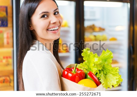 I choose organic products. Beautiful young woman holding shopping bag with fruits and smiling while standing in grocery store near refrigerator   - stock photo