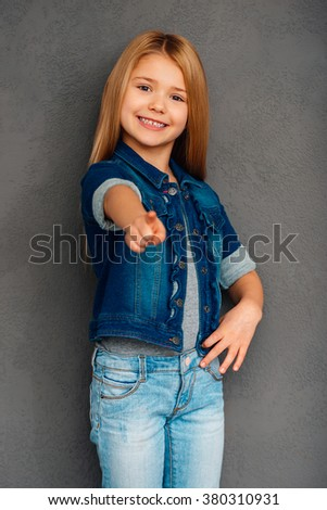 I choose you! Cheerful littlegirl pointing you and looking at camera with smile while standing against grey background - stock photo