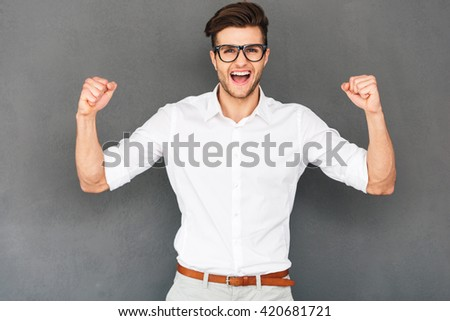 I did it! Cheerful young man gesturing and keeping his mouth open while standing against grey background - stock photo