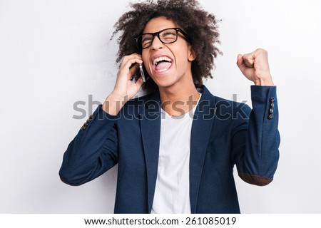 I did it! Handsome young African man holding mobile phone and gesturing while standing against grey background  - stock photo
