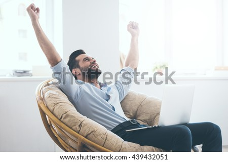 I did it! Handsome young man keeping arms raised and looking happy while sitting in a big comfortable chair at home with laptop laying on his knees - stock photo