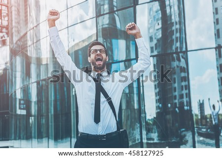 I did it! Happy young businessman keeping arms raised and expressing positivity while standing outdoors