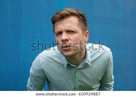 I don't know. Portrait of doubtful caucasian male wearing casual blue shirt,  looking with indecisive expression on his face, showing doubt and hesitation. Body language