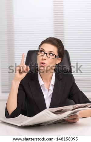 I�¯�¿�½e got an idea! Confident middle-aged woman in glasses sitting at her working place and gesturing while reading a newspaper - stock photo