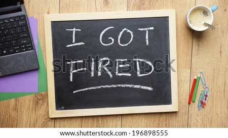 I god fired written on a chalkboard at the office - stock photo