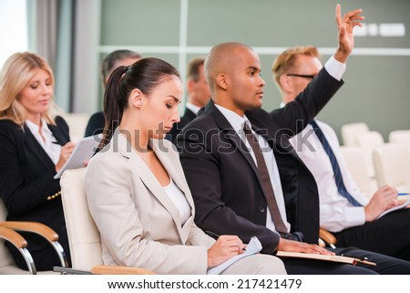 I have a question! Group of business people in formalwear sitting at the chairs in conference hall and writing something gin their note pads while handsome African man raising his arm - stock photo