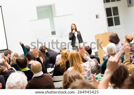 I have a question. Group of people sitting at the chairs in conference hall, raising their hands. Workshop at university. Business and Entrepreneurship event. - stock photo