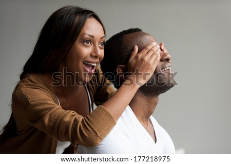 I have a surprise for you! Beautiful young African woman covering her boyfriend eyes with hands and smiling while isolated on grey background  - stock photo