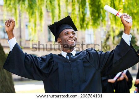 I have finally graduated! Happy young African man in graduation gowns holding diploma and rising arms up while his friends standing in the background  - stock photo