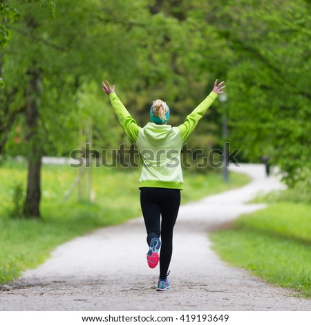 I have made it. Sporty young female runner arms rised in city park.  Running woman during outdoor workout in nature. Fitness model outdoors. Weight Loss. Healthy lifestyle.  - stock photo