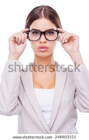 I have my own vision of business. Confident young businesswoman adjusting her glasses while standing against white background - stock photo