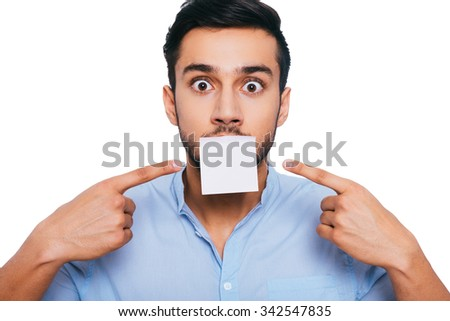 I have nothing to say except this... Shocked young Indian man pointing adhesive note on his mouth and staring at you while standing against white background - stock photo