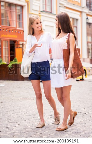 I have so much to tell you! Two beautiful young women walking along the street and talking  - stock photo