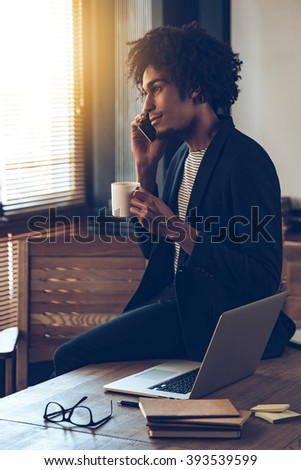 I have some great news for you! Side view of young handsome African man talking on mobile phone and holding coffee cup while sitting on table at his working place - stock photo