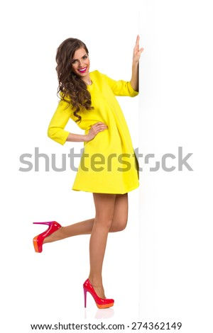 I Hold Banner For You. Smiling beautiful young woman in yellow dress and red high heels standing on one leg and holding a big placard in one hand. Full length studio shot isolated on white. - stock photo