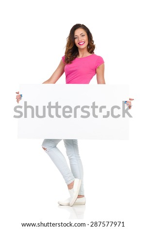I Hold Your Placard. Smiling young woman in torn jeans and pink shirt standing and holding white paper sheet. Full length studio shot isolated on white - stock photo