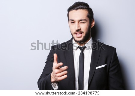 I hope we understand each other. Joyful young man in formalwear winking and pointing on you while standing against grey background