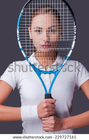 I know how to win! Beautiful young women in sports clothes holding tennis racket in front of her face and looking at camera while standing against grey background - stock photo