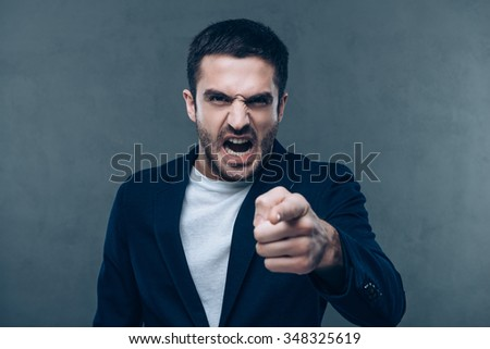 I know that was you! Furious young man looking at camera and pointing you while standing against grey background