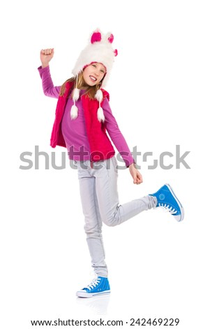 I like my fur hat. Girl in funny fur hat is standing on one leg with arm raised. Full length length studio shot isolated on white. - stock photo
