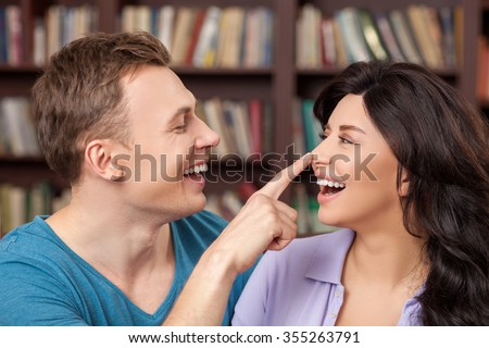 I like spending time with you. Beautiful young loving couple is dating and embracing in the library. They are laughing. The man is touching female nose with joy - stock photo
