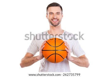 I love basketball. Confident young man holding basketball ball and smiling while standing against white background  - stock photo