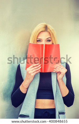 I love book. Blonde Eastern European Woman holding opened book, covering face, thinking, wearing long vest, black fitted T shirt, standing by metal silver wall in New York. Instagram filtered effect. - stock photo