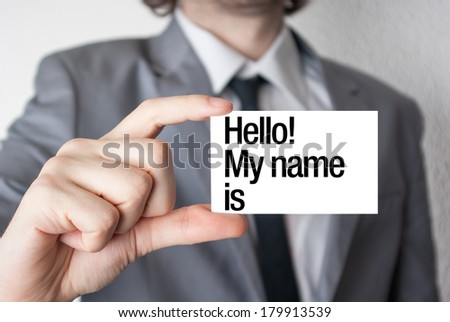 I love business. Businessman in suit with a black tie showing or holding business card - stock photo