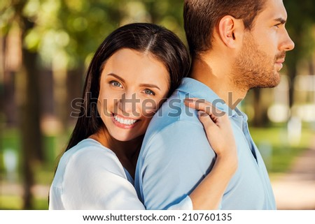 I love him so much! Beautiful young woman leaning to the back of her boyfriend and smiling at camera while both standing outdoors  - stock photo