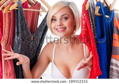 I love my clothes! Beautiful young blond hair woman looking out from the dresses in closet - stock photo