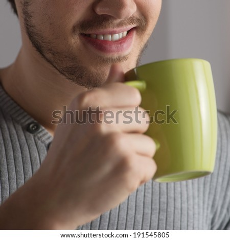 I love my coffee. A handsome young man smiling while holding a cup of coffee - stock photo