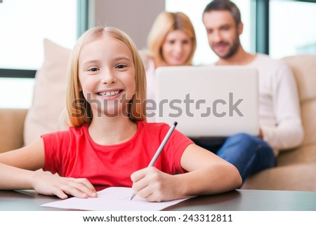 I love my family! Happy little girl drawing something on paper and smiling while her parents sitting in the background with laptop  - stock photo