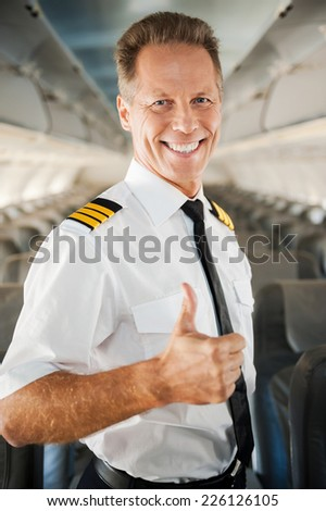 I love my job! Confident male pilot in uniform showing his thumb up and smiling while standing inside of the airplane - stock photo