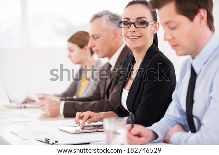 I love my job! Side view of confident business people sitting in a row at the table while attractive woman looking at camera and smiling - stock photo